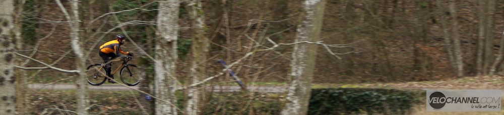 vélo de loin derrière des branches